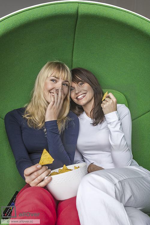 Zwei junge Frauen sitzen in gruenem Kugelsessel und naschen Chips (model-released)