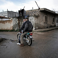 SYRIA - Al Qsair. A Syrian reporter ride a motorbike in Al Qsair, on January 28,  2012. Al Qsair is a small town of 40000 inhabitants, located 25Km south-west of Homs. The town is besieged since the beginning of November and so far it counts 65 dead.In all Syria there are hundreds of non-professional reporters who without experience and without proper gear keep documenting, day after day, the crackdown of the regime. This series of pictures is dedicated to them... to this colleagues who among every kind of difficulties and risks let know to the word their stories and drama.  ALESSIO ROMENZI