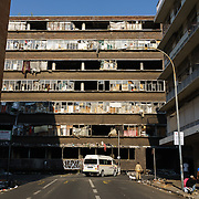"A fire-damaged ""hijacked building"" (illegally occupied squat) in downtown Johannesburg, South Africa. After a steep decline in the 1990s, the inner city is now a peculiar mix of interspersed working class, down-and-out and gentrified realities, all within a few minutes walk of each other."