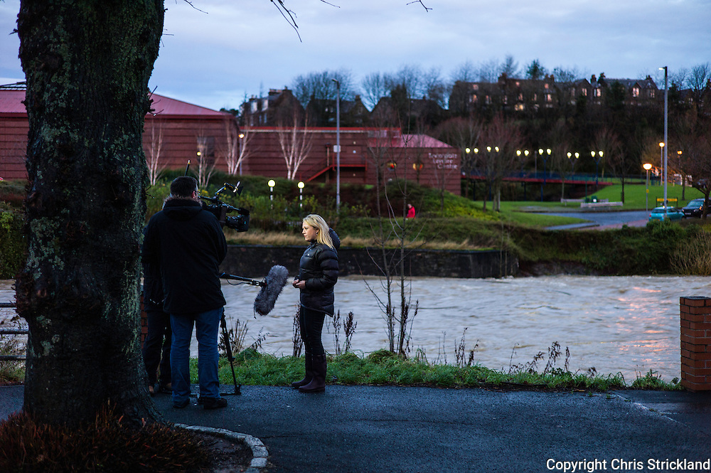 Hawick, Scotland, UK. 6th December 2015. A TV news crew broadcast next to the River Teviot. The building in the backdrop, The Teviotdale Leisure centre, was used as a rest centre for evacuated residents and volunteers.