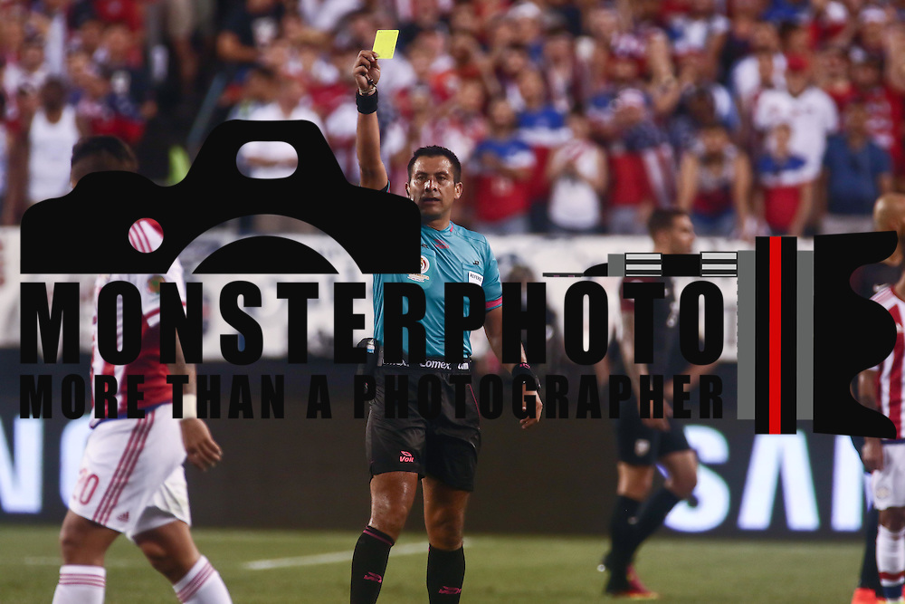 Referee JULIO BASCUÑAN, left, issues a yellow card to United States Defender DEANDRE YEDLIN (2) in the first half of a Copa America Centenario Group A match between the United States and Paraguay Saturday, June. 11, 2016 at Lincoln Financial Field in Philadelphia, PA.