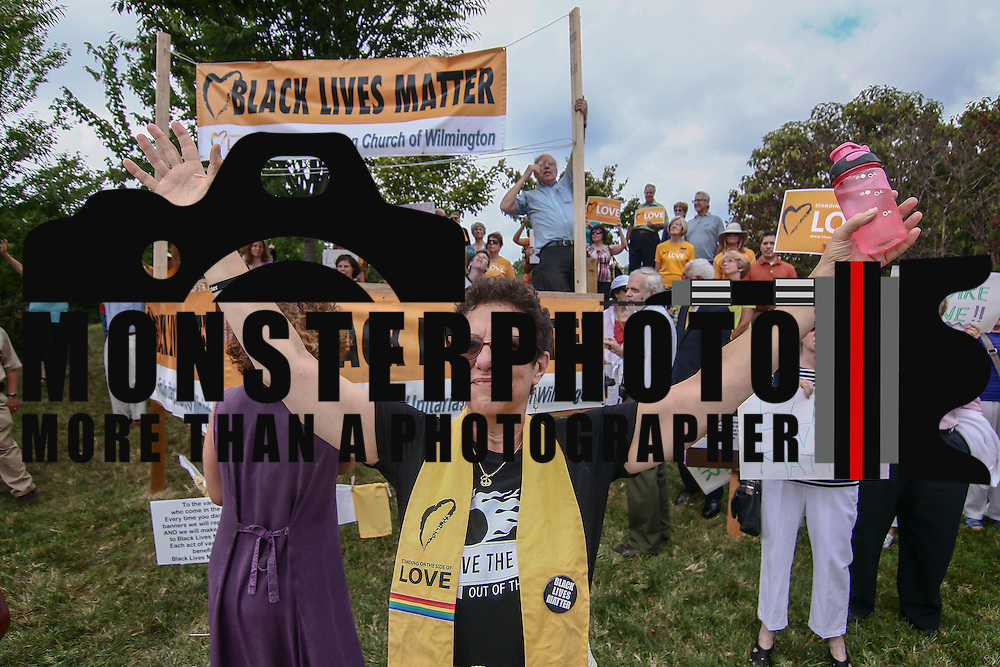 Rev. Roberta Finkelstein holds up her hands in prayer during a rededication ceremony for its Black Lives Matter banners Sunday, August 21, 2016, at First Unitarian Church in Wilmington.