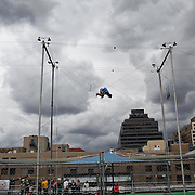 Instructor Zack Bodinger demonstrates a trick at Trapeze School New York during the June 4th morning class. The two hour beginner session taught the nine students in attendance the basics of flying trapeze -- including knee hangs and backwards somersaults -- in their facility on the roof of Pier 40...CREDIT: Daniella Zalcman for The Wall Street Journal.SLUG: NYMETROMONEY_Trapeze