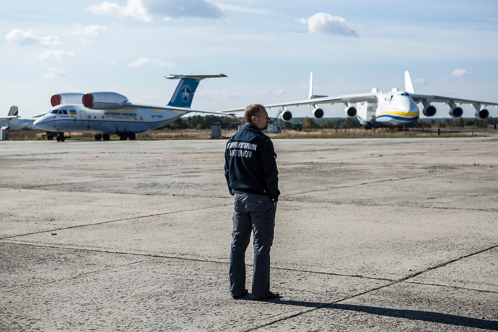 GOSTOMEL, UKRAINE - OCTOBER 1, 2014: An Antonov employee looks out on an airfield where the Antonov AN-225, the longest and heaviest airplane ever built, at right, is parked in Gostomel, outside Kiev, Ukraine. CREDIT: Brendan Hoffman for The New York Times