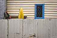 blue window and weatherboard, with kayak, behind rusty fence
