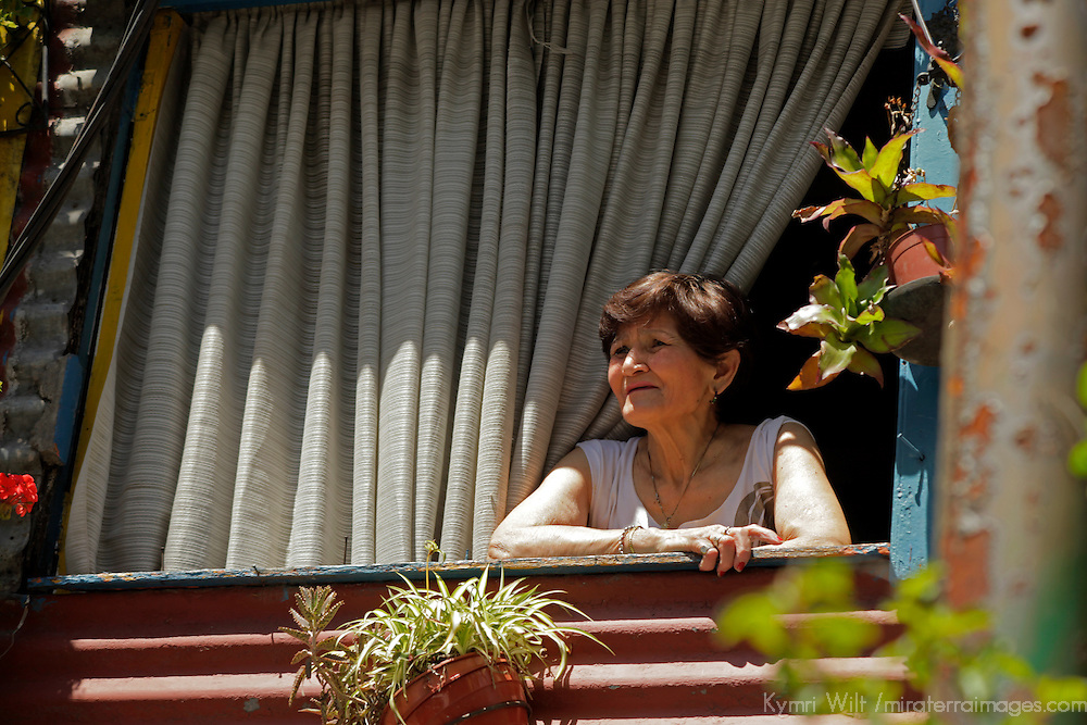 South America, Argentina, Buenos Aires. Woman looking out of her window in La Boca.