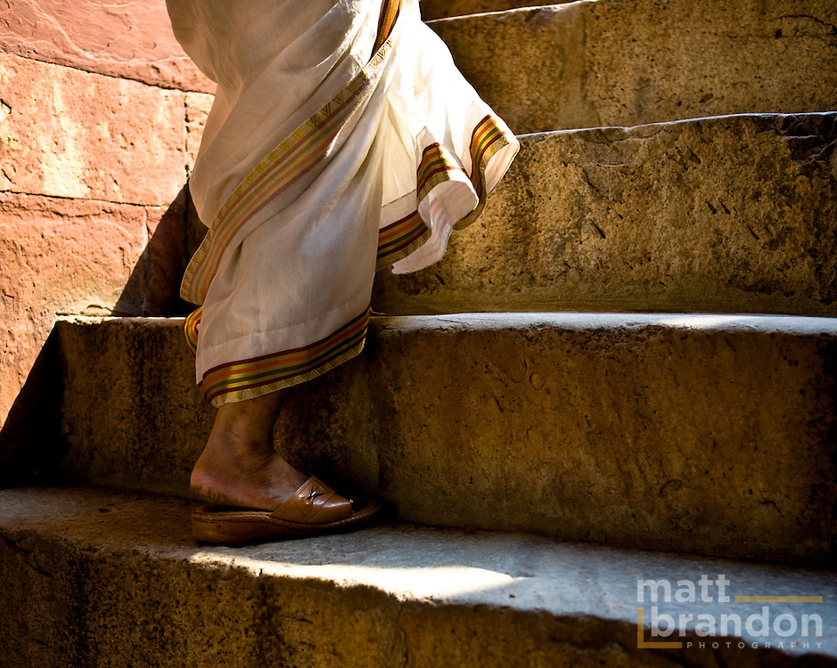 A close-up of a woman's feet walking up the steps and a sorry at humayun's tomb.
