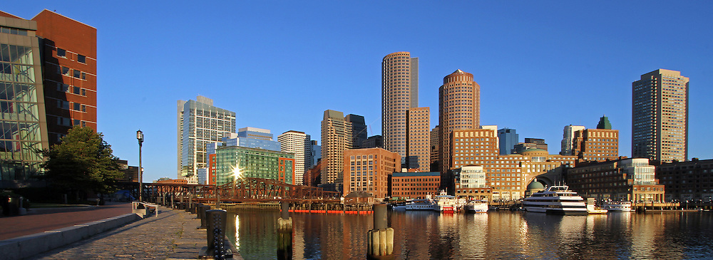 Boston skyline panorama photography from New England based award winning fine art photographer Juergen Roth showing landmarks such as Boston Downtown, Boston Harbor, Financial District, US Coast Guard, National Oceanic and Atmospheric Administration, Rowes Wharf, One International Place, Fan Pier, Odyssey cruise ship and the Boston harbor hotel as seen from the Boston Harbor walk at Fan Pier. <br />