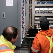 Joe Marquez (right) and Rick Gagné of the Ontario Clean Water Agency (OCWA) examining the Programmable Logic Controller (PLC) of the water treatment plant at the Ochiichagwe'Babigo'Ining Ojibway Nation reserve (also known as the Dalles First Nation) in Northern Ontario, Canada on 19 December 2016. The OCWA representatives had been tasked with assessing what needs to be done to connect the plant's systems via the Internet to a central monitoring facility being established at the Bimose Tribal Council in the nearby town of Kenora.
