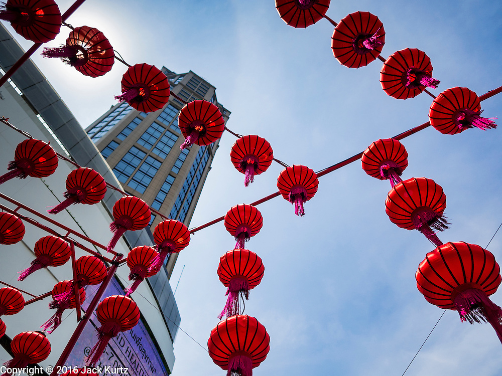 "07 FEBRUARY 2016 - BANGKOK, THAILAND: Chinese New Year lanterns hang over the entrance to Emporium, a high end shopping mall on Sukhumvit Road in Bangkok. Chinese New Year, also called Lunar New Year or Tet (in Vietnamese communities) starts Monday February 8. The coming year will be the ""Year of the Monkey."" Thailand has the largest overseas Chinese population in the world; about 14 percent of Thais are of Chinese ancestry and some Chinese holidays, especially Chinese New Year, are widely celebrated in Thailand.        PHOTO BY JACK KURTZ"