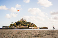 A young girl flies a kite on the beach in front of St Michael's Mount, August 2014.