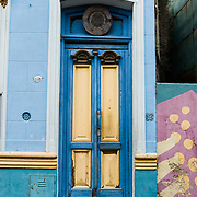 """Blue and yellow painted wood double doors in San Telmo barrio, the heart of old Buenos Aires, Argentina, South America. Admire well-preserved old buildings in San Telmo (""""Saint Pedro González Telmo""""), the oldest barrio (neighborhood) of Buenos Aires, in Argentina, South America."""