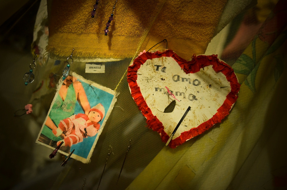 """A handmade card that says, """"I love you mom"""" hangs on the mosquito net that covers Marta Eugenia Cortez's bed that she shares with her 2-year old daughter, Ivana, inside Illopango Womens' prison in San Salvador, El Salvador.  Cortez is serving a prison sentence after being convicted for committing extortion crimes."""