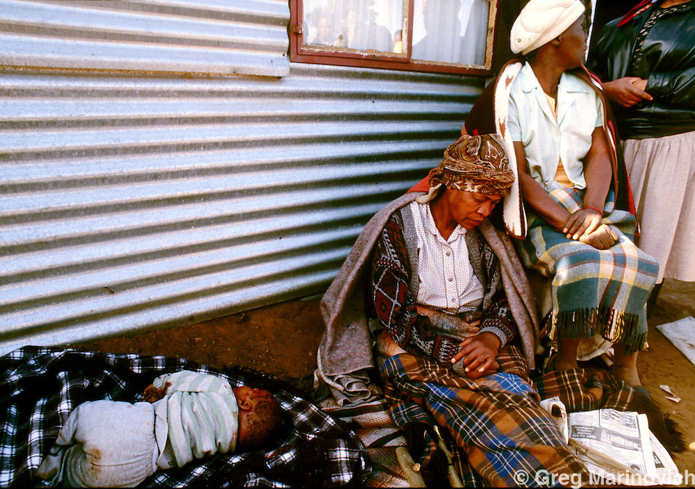 IPMG0040 South Africa, Boipatong, 1992..The aunt of nine month old Aaron Mathope sits next to his body in Boipatong township south of Johannesburg June 1992 on the day 45 people were killed by Inkatha Freedom Party supporting Zulus.  Aaron and his mother were hacked to death, and the Truth & Reconciliation Commission found both Inkatha and the security forces of the then-white regime responsible.  .Photograph by Greg Marinovich/South Photographs