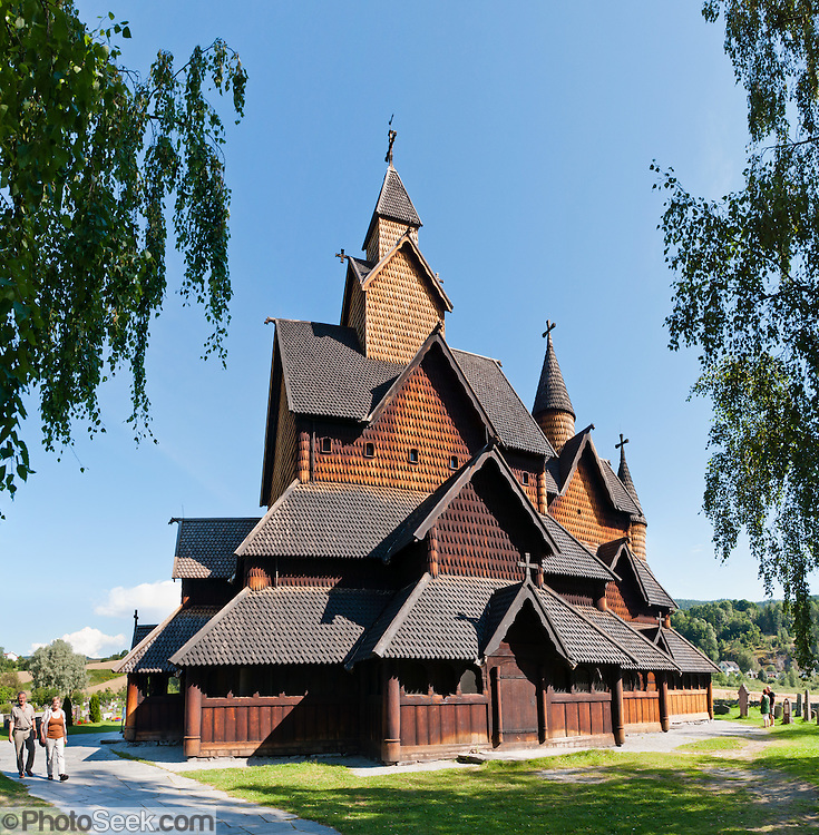 """A couple of people walk beside Heddal stave church, Norway's largest stave church. This triple nave stave church, which some call """"a Gothic cathedral in wood,"""" was built in the early 13th century and restored in 1849-1851 and the 1950s. Heddal stavkirke is in Notodden municipality, Telemark County, Norway. Panorama stitched from 6 overlapping photos."""