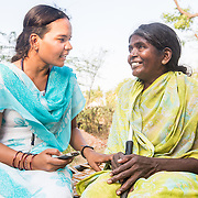 CAPTION: Gathering PIMMS data. Mobility India and CBM have partnered with Aptivate to develop a simple means of collecting key project-relevant data using relatively unsophisticated mobile phones. LOCATION: Sappayyanapura (village), Kasaba (hobli), Chamrajnagar (district), Karnataka (state), India. INDIVIDUAL(S) PHOTOGRAPHED: Left: Sudhamani R.; right: Doddamma.