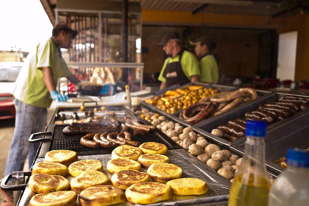 Outdoor restaurant serving longaniza, blood sausage, arepas, patacones, and various meats in Sutamarchán, Boyacá, Colombia.