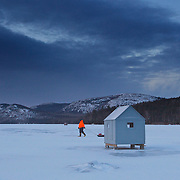 An ice fisherman pulls his sled filled with the day's supplies to his ice fishing shack on Eagle Lake in Acadia National Park. It's a typical midwinter morning in downeast Maine with the temperature at 1 degree F and a wind chill of -15F.