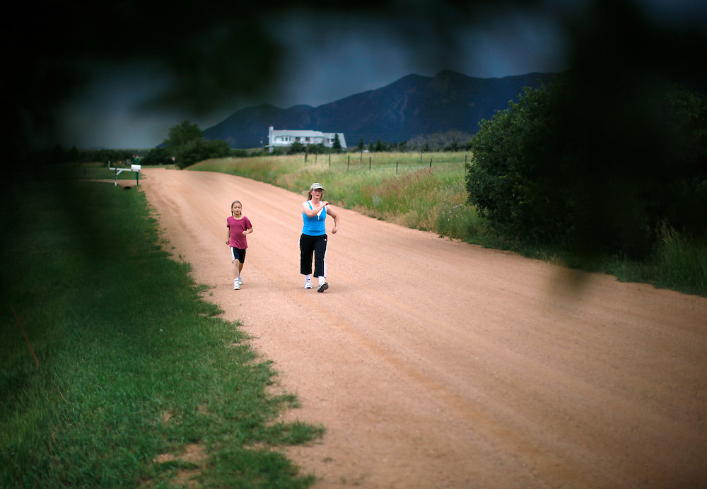 Wendy Jeub, mother of 15 power walks with daughter Tabitha (L) near their home in Monument, Colorado July 19, 2009. Wendy has written cookbooks and diet books sharing her secrets for staying in shape after that many children. Quiverfull believers Wendy and Chris Jeub would be happy to have more kids if God wills it they say. REUTERS/Rick Wilking (UNITED STATES)