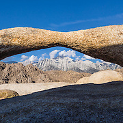 Lathe Arch frames Lone Pine Peak (12,943 ft) in BLM Alabama Hills Recreation Area on the eastern slope of the Sierra Nevada Mountains in the Owens Valley, west of Lone Pine in Inyo County, California, USA. The Alabama Hills are a popular filming location for television and movie productions (such as Gunga Din, Gladiator, Iron Man,  Transformers: Revenge of the Fallen), especially Westerns (Tom Mix films, Hopalong Cassidy films, The Gene Autry Show, The Lone Ranger, Bonanza, How the West Was Won, and Joe Kidd). Two main types of rock are exposed at Alabama Hills: 1) orange, drab weathered metamorphosed volcanic rock 150-200 million years old; and 2) 82- to 85-million-year-old biotite monzogranite which weathers to potato-shaped large boulders.  This panorama was stitched from 3 overlapping photos.