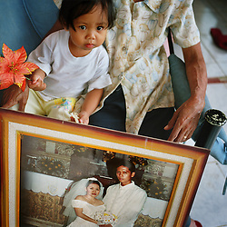 """Precious Lara sits with the wedding photograph of her parents Rosalie and Christopher Villanueva in their home in Cavite, Philippines on Dec. 2006.  Teresita """"Tita"""" and Demetrio """"Emmet"""" Comodaz takes care of their granddaughter while their daughter Rosalie, 35, works as a nurse in the United Arab Emirates. Precious Lara has not spent much time with either of her parents since her birth and have thus bonded with Tita and Emmet instead. Isolation from family members is a severe issue for Overseas Filipino Workers."""