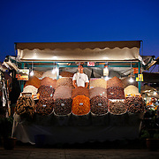 """SHOT 11/1/09 12:05:52 PM - A vendor at a food stall in the Djemaa el Fna in Marrakech or Marrakesh, Morocco as the sun sets. Marrakech is known as the """"Red City"""", is an important and former imperial city in Morocco. It has a population of 1,070,838 (as of 2004), and is the capital of the mid-southwestern economic region of Marrakech-Tensift-Al Haouz, near the foothills of the snow-capped Atlas Mountains. Like many North African and Middle Eastern cities, Marrakech comprises both an old fortified city (the médina) and an adjacent modern city (called Gueliz). Marrakech has the largest traditional market (souk) in Morocco and also has one of the busiest squares in Africa and the world, Djemaa el Fna.[2] The square bustles with acrobats, story-tellers, water sellers, dancers, and musicians. By night, the square turns into food stalls, becoming a huge open-air restaurant. Morocco, officially the Kingdom of Morocco is a country located in North Africa with a population of nearly 32 million people and an area just under 173,000 squrare miles.(Photo by Marc Piscotty / © 2009)"""