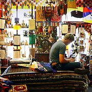 SHOT 7/1/11 1:14:31 PM - Phillip Inge of Boulder, Co. works at the Tibet Gallery in Boulder, Co. Tibet Gallery promotes itself as the ultimate collection of Tibetan handicrafts, artifacts, incense, buddha statues, thangkas rugs and dharma products. A prayer flag is a colorful panel of rectangular cloth, often found strung along mountain ridges and peaks high in the Himalayas. They are used to bless the surrounding countryside and for other purposes. Prayer flags are believed to have originated with Bön, which predated Buddhism in Tibet.Boulder, Co. has long been  famous for residents who are über environmentally conscious, socially liberal, obsessively healthy and, at times, overly preachy about each. It also has been a haven for Eastern philosophy and thought including a 1,000-student Buddhist-inspired university, yoga studios and meditation centers by the dozens, scads of alternative medicine practitioners, authentic Himalayan restaurants and more Eastern import shops than you'd think a town of 100,000 could possibly sustain.  (Photo by Marc Piscotty / © 2011)