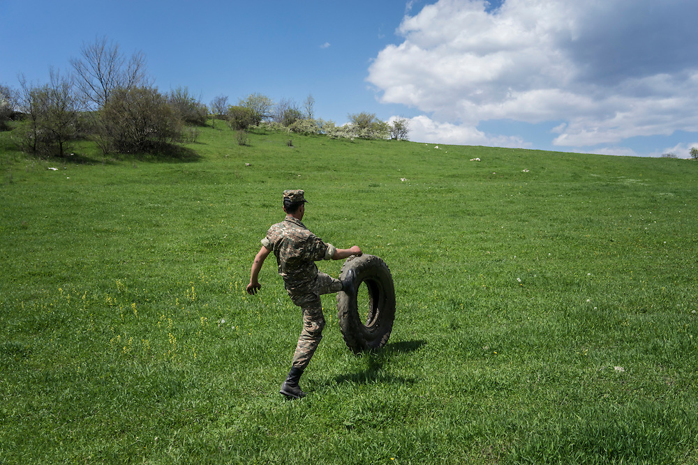KARASHEN, NAGORNO-KARABAKH - APRIL 19: Shavalat Sargsyan, a 20-year-old Armenian soldier from Spitak, rolls a truck tire up a hill where he was instructed to take it for disposal on April 19, 2015 in Karashen, Nagorno-Karabakh. Since signing a ceasefire in a war with Azerbaijan in 1994, Nagorno-Karabakh, officially part of Azerbaijan, has functioned as a self-declared independent republic and de facto part of Armenia, with hostilities along the line of contact between Nagorno-Karabakh and Azerbaijan occasionally flaring up and causing casualties. (Photo by Brendan Hoffman/Getty Images) *** Local Caption *** Samson Israelyan; Narek Martirosyan