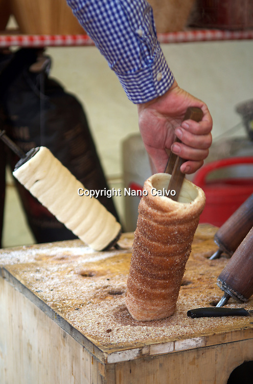 Kürtőskalács or Chimney Cake. Traditional costumes and folk traditions at Easter Festival in Hollókő, UNESCO World Heritage-listed village in the Cserhát Hills of the Northern Uplands, Hungary.