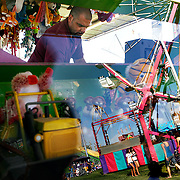 """Fairgoers at the midway are reflected in the glass case of the """"Mighty Payloader"""" as Shawn, who didn't want to give his last name, tends the booth at the 2010 Benton Franklin Fair & Rodeo."""