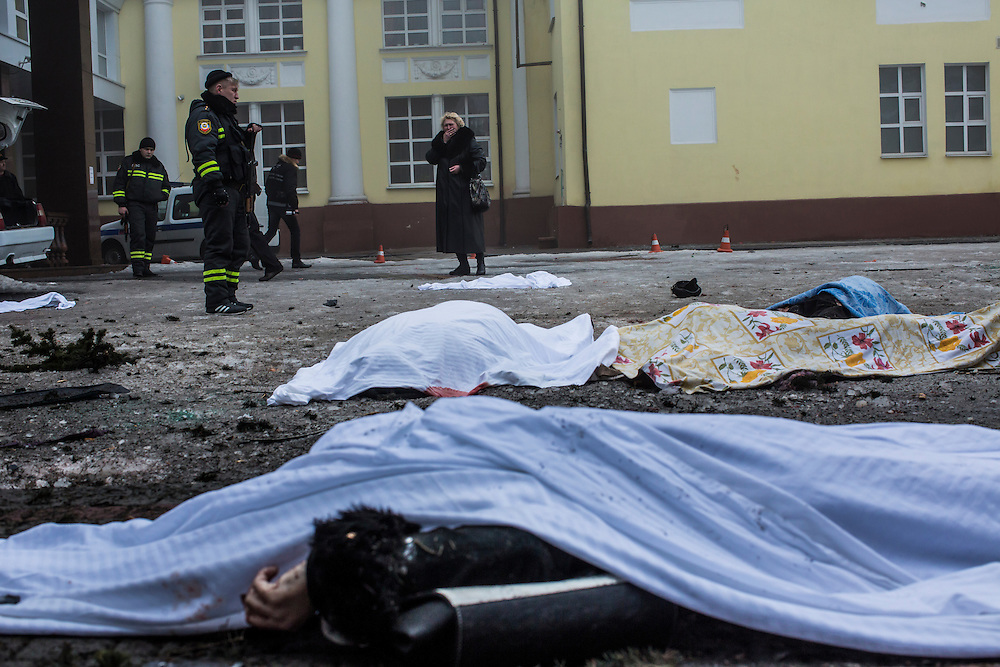 DONETSK, UKRAINE - JANUARY 30, 2015: A woman cries as she looks at the bodies of four people who were killed when a rocket struck the parking lot outside a center where humanitarian aid was being distributed in Donetsk, Ukraine. A fifth person was killed in a parked car, and at least two others died in a separate shelling nearby. CREDIT: Brendan Hoffman for The New York Times