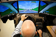Steve Woodward, staff psychologist at the National Center for PTSD, left, tries out a driving simulator in Palo Alto, Calif., December 15, 2011.