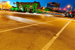 Kansas City's Union Station lit green for Veteran's Day, 2015. Intersection of Pershing and Main in foreground with traffic motion.