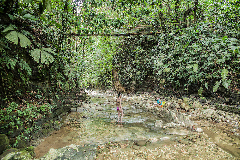 Visitors enjoy a bath at the river inside Finca Bellavista property