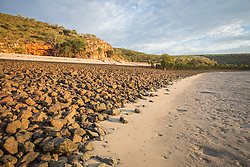 Evening strikes the red sandstone at the back of a beach on Macleay Island on the Kimberley coast.
