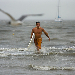 A surfer heads out the water after trying to catch some waves generated by Tropical Storm Aberto in Cedar Key, Florida June12, 2006. REUTERS/Scott Audette