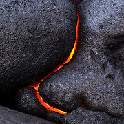 Molten lava makes dramatic curved patterns as it breaks through solid rock in Volcanoes National Park, Hawaii.