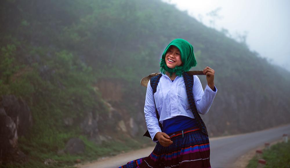 A girl in the early morning mist near Bac Ha, Vietnam.