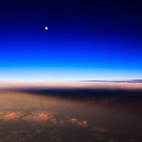 Aerial view of the moon rising over clouds illuminated by the last rays of the setting sun.