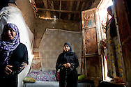 Aya, center, and her sister, Sabryn, left, stand in the entrance of the home they live in with their mother in a slum in Manshiet Nasser, adjacent to a government housing project on the eastern outskirts of Cairo, on October 5, 2011. According to many of the slum's residents living in the shadows of the housing project, they were promised rooms in the complex three years ago by government. Residents of the slums are cut off from basic public services such as waste management and water supply. Ann Hermes/© The Christian Science Monitor 2011