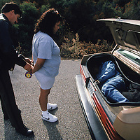A smuggler is arrested in California, after four people were found in the trunk of her car on a road used to bypass a checkpoint installed during operation Gatekeeper. A 1997 study by the University of Houston attributed rise in undocumented migrant deaths to Operation Gatekeeper.