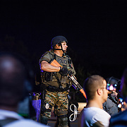 A Police Officer stands on a barrie to overlook the crowd after an incident at one end of the designated protest block during continued demonstrations in Ferguson, Mo. on August 19th, 2014. (Samuel Corum/Legion Photo)