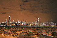Ice swirls form in the harbor as the Chicago skyline looms large on a cold and windy winter night along Lake Michigan.
