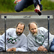Portland State University track coaches and siblings Keith and Ken Woodard are hurdled by Kristen Hall.