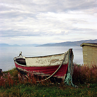 Red and white rowing boat on the lake beach