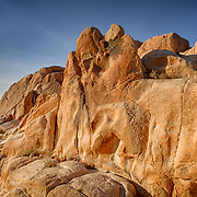 USA, California, Joshua Tree National Park. Sun rises over a rock formation.