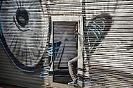 Joven se resguarda en su tienda mientras termina el enfrentamiento entre encapuchados y carabineros, en las cercanías de la estación Mapocho, Santiago de Chile.