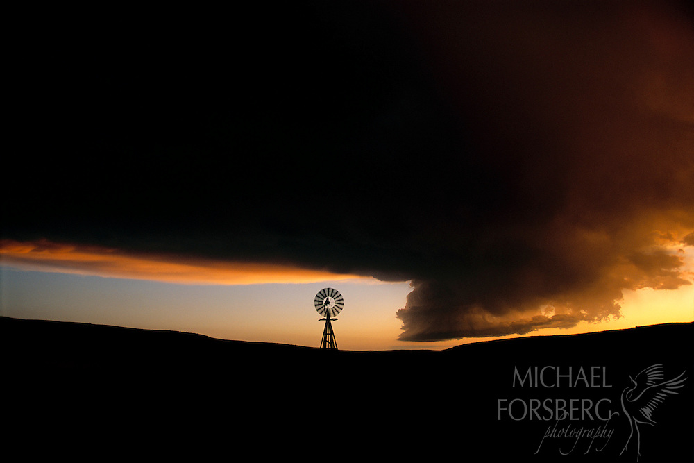 Nebraska Sandhills. At sundown, a lone sandhills windmill stands strong in silhouette as a wall cloud looms on the western horizon. Later that same evening, as they often do, this wall cloud turned into a tornado.