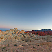 The earth's shadow and the crescent moon are visible over the large silica dome and the fire canyon, located in the Valley of Fire, Nevada.
