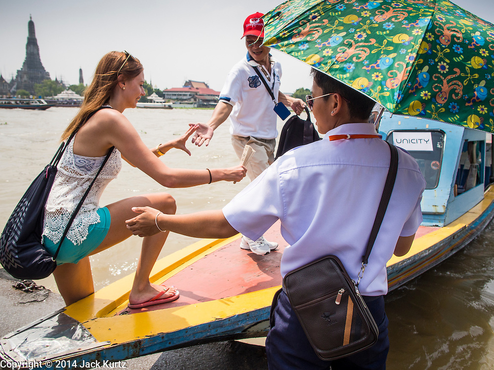 15 OCTOBER 2014 - BANGKOK, THAILAND:  A tour guide (red hat) helps a woman board a tour boat on the Chao Phraya River near Wat Pho in Bangkok. The number of tourists arriving in Thailand in July fell 10.9 per cent from a year earlier, according to data from the Department of Tourism. The drop in arrivals is being blamed on continued uncertainty about Thailand's political situation. The tourist sector accounts for about 10 per cent of the Thai economy and suffered its biggest drop in visitors in June - the first full month after the army took power on May 22. Arrivals for the year to date are down 10.7% over the same period last year.   PHOTO BY JACK KURTZ